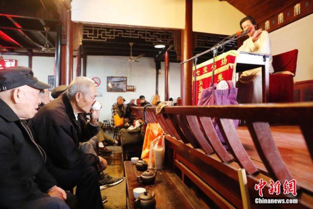 Mit Blick auf die Darstellerin auf der Bühne trinkt ein begeisterter Zuhörer seinen Tee