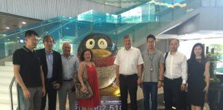 Die Besucher mit Unternehmensvertreter Evan ZHOU (3.v.r.) vor dem Unternehmenslogo Pinguin